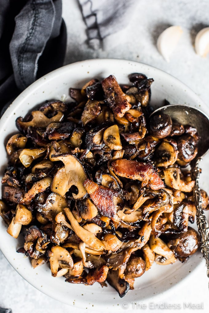 These crazy delicious Garlic Bacon Mushrooms are the ultimate side dish. They're easy enough to make as a weeknight side yet tasty enough to serve alongside a Thanksgiving or Christmas dinner. This recipe is also 100% gluten-free + paleo + Whole30 approved. Dig in, my friends! | theendlessmeal.com | #mushrooms #sidedish #paleo #whole30 #recipe #bacon #thanksgiving #ThanksgivingRecipes #thanksgivingsides #christmasrecipes