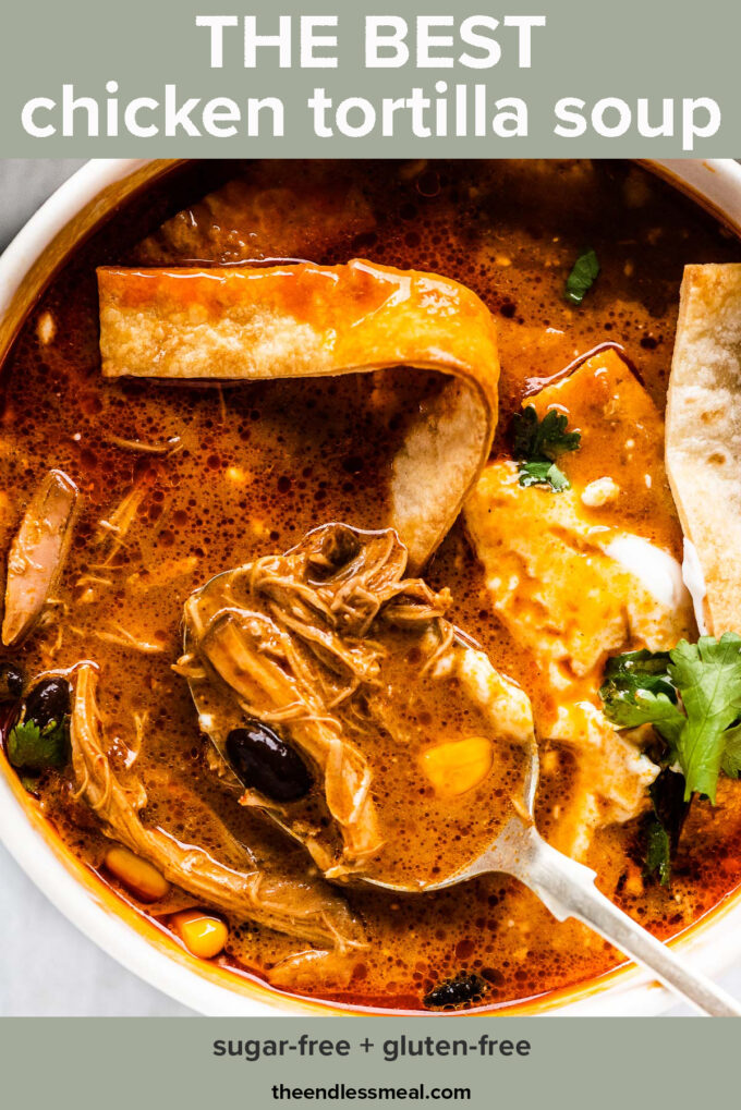 Chicken tortilla soup stirred up with some sour cream in a bowl with the recipe title on top of the picture.