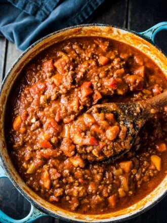 A pot of bean-free paleo sweet potato chili with a wooden spoon in it.