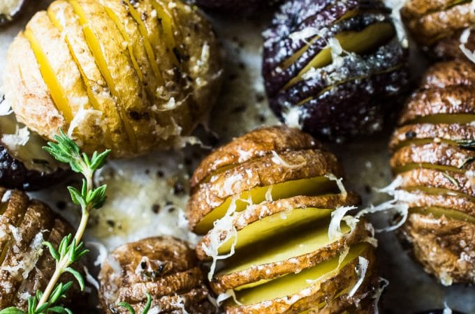 These pretty Mini Hasselback Potatoes are as delicious as can be. The little cuts get nice and crispy while the insides are soft and creamy. They're dusted with thyme leaves and sea salt and served with roasted garlic. Whether you're serving Thanksgiving or Christmas dinner, or want a gorgeous and easy to make side dish, these healthy potatoes will fit the bill. | theendlessmeal.com