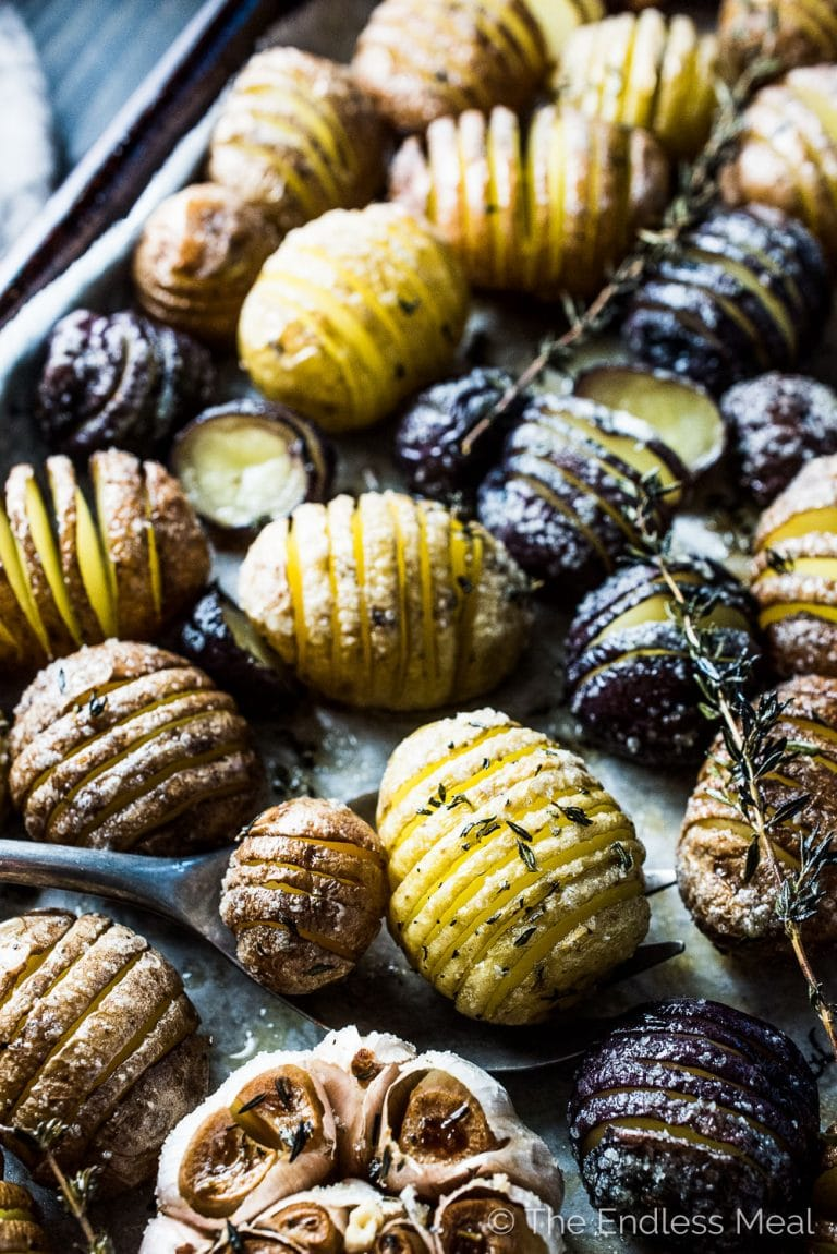 These pretty Mini Hasselback Potatoes are as delicious as can be. The little cuts get nice and crispy while the insides are soft and creamy. They're dusted with thyme leaves and sea salt and served with roasted garlic. Whether you're serving Thanksgiving or Christmas dinner, or want a gorgeous and easy to make side dish, this healthy potato recipe will fit the bill.   theendlessmeal.com