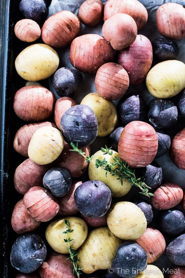 These pretty Mini Hasselback Potatoes are as delicious as can be. The little cuts get nice and crispy while the insides are soft and creamy. They're dusted with thyme leaves and sea salt and served with roasted garlic. Whether you're serving Thanksgiving or Christmas dinner, or want a gorgeous and easy to make side dish, this healthy potato recipe will fit the bill. | theendlessmeal.com