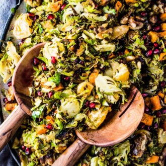 Roasted Shaved Brussels Sprout Salad on a platter with 2 wooden salad tons in it.