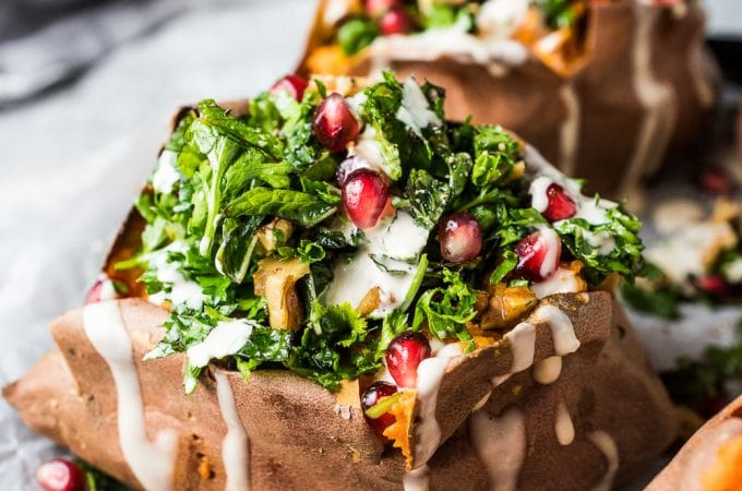 These baked Stuffed Sweet Potatoes are piled high with toasted walnuts, fresh herbs, and crunchy pomegranate seeds. A drizzle of easy to make tahini sauce takes them over the top. They're a healthy side dish or main course vegetarian recipe. They're also naturally vegan + gluten-free + paleo + Whole30 compliant. | theendlessmeal.com