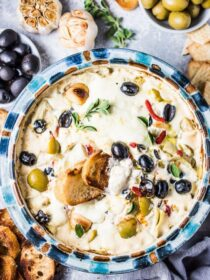 SAVE FOR LATER! Looking for the ultimate party dip? You are in the right place, my friend! This delicious Roasted Garlic Artichoke Olive Dip is completely addicting. It's a grownup version of a spinach and artichoke dip. This pot of creamy melted cheese is dotted with green and black olives, roasted garlic, quartered artichoke hearts, and roasted red peppers. You will LOVE it! #theendlessmeal #olives #dip #olivedip #artichokedip #roastedgarlic #christmas #partyrecipes #healthyrecipes