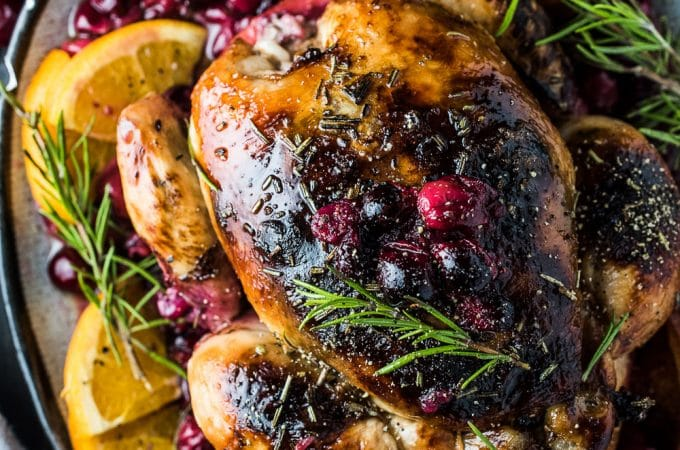 This crazy delicious Orange Cranberry Roast Chicken is covered with rosemary balsamic butter to keep it tender and juicy. It's a super easy to make and healthy recipe that is as perfect for a weekend dinner as it is for a special holiday meal.  | www.theendlessmeal.com