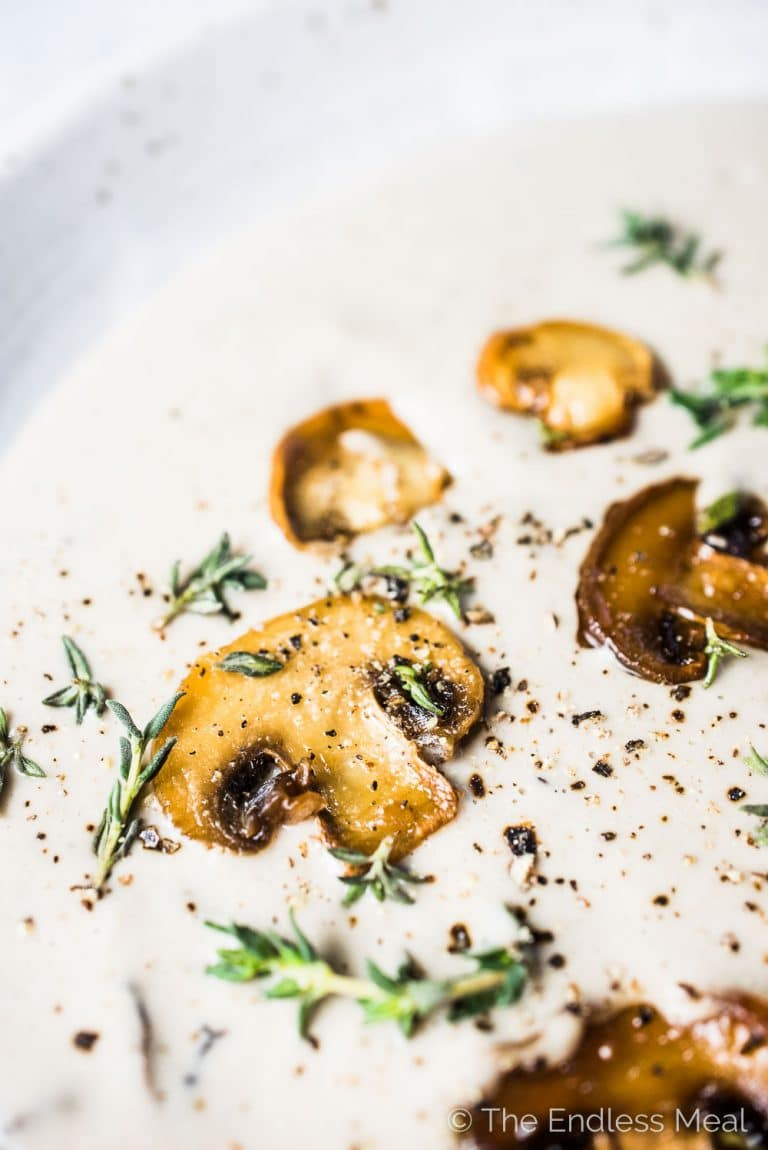 A close up of a bowl of cashew cream of mushroom soup with sautéed mushrooms and some thyme on top.