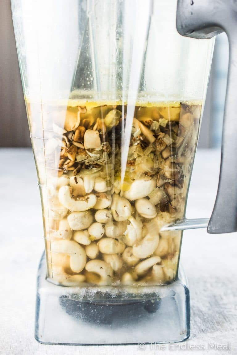A picture of a blender with the cashews and mushrooms inside before they get blended to make cashew cream of mushroom soup.