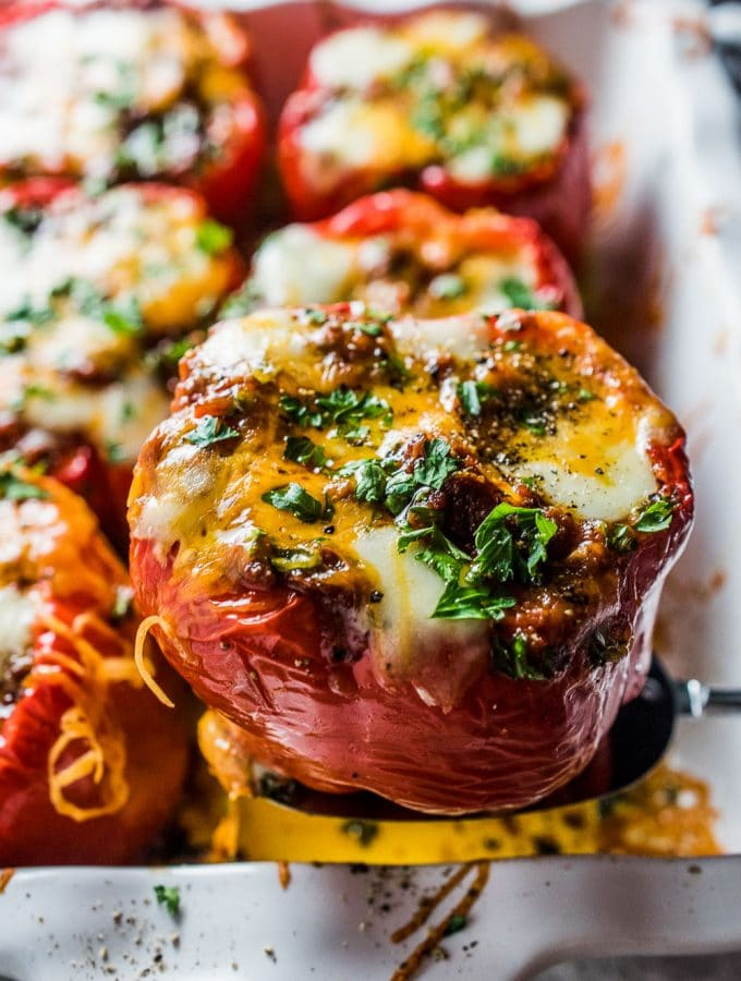 A ladle picking up one of the chili stuffed peppers with lots of melted cheese.