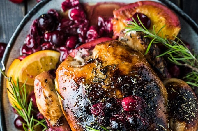This crazy delicious Orange Cranberry Roast Chicken is covered with rosemary balsamic butter to keep it tender and juicy. It's a super easy to make and healthy recipe that is as perfect for a weekend dinner as it is for a special holiday meal. | The Endless Meal