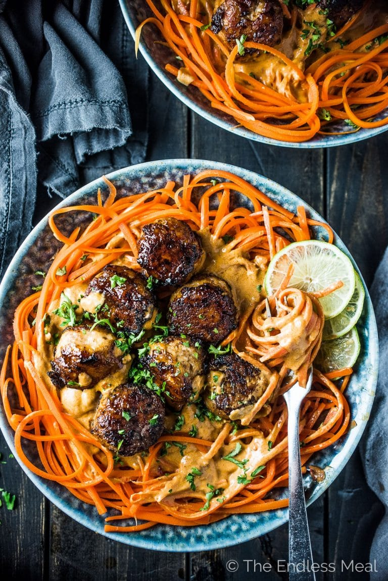 Thai Chicken Curry Meatballs are served over carrot noodles with coconut satay sauce. They are a crazy delicious and healthy dinner recipe that won't leave you feeling like you're missing out. They're You will LOVE them! | theendlessmeal.com | #meatballs #chickenmeatballs #thaifood #healthyrecipes #carrots #LOVaHealthierYou #lovidia #sponsored