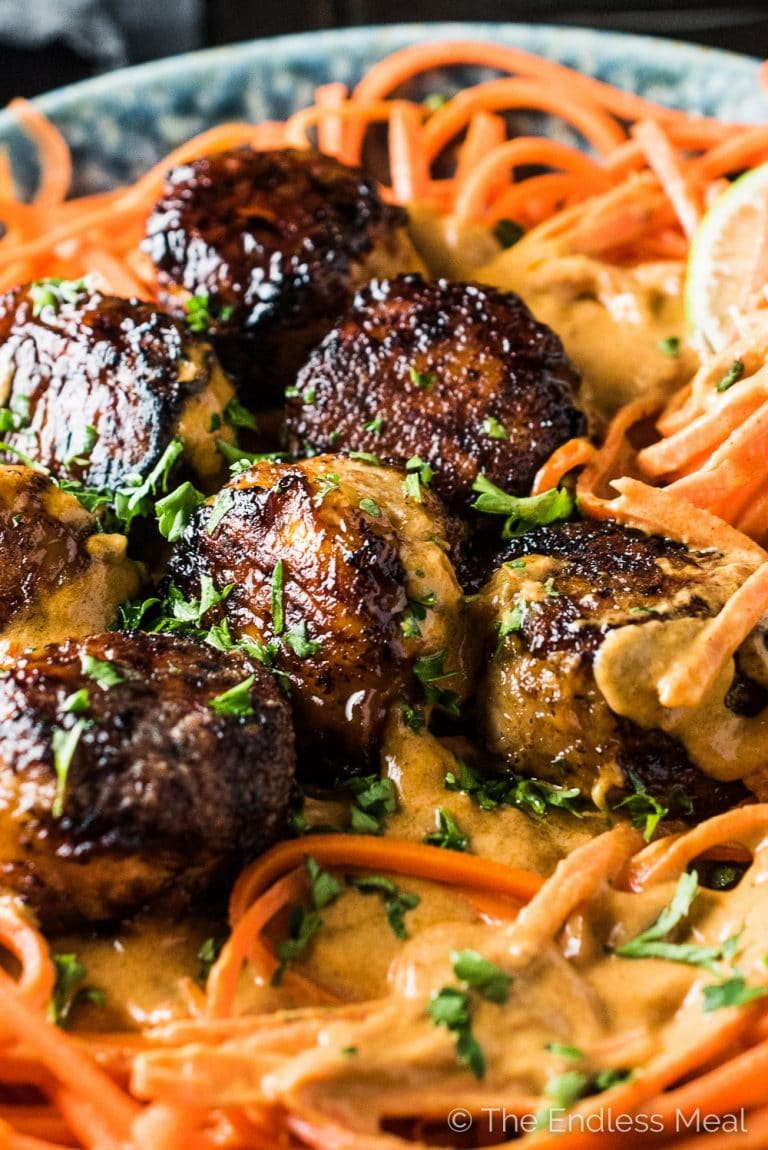 Thai Chicken Curry Meatballs are served over carrot noodles with coconut satay sauce. They are a crazy delicious and healthy dinner recipe that won't leave you feeling like you're missing out. Go ahead, help yourself to seconds! | theendlessmeal.com