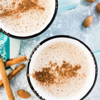 2 almond butter lattes in blue mugs with cinnamon sprinkled on top.