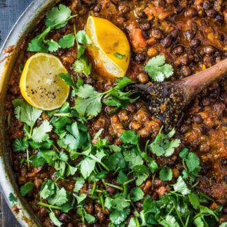 A pot of black chana masala with a wooden spoon in it and some cilantro on the top.