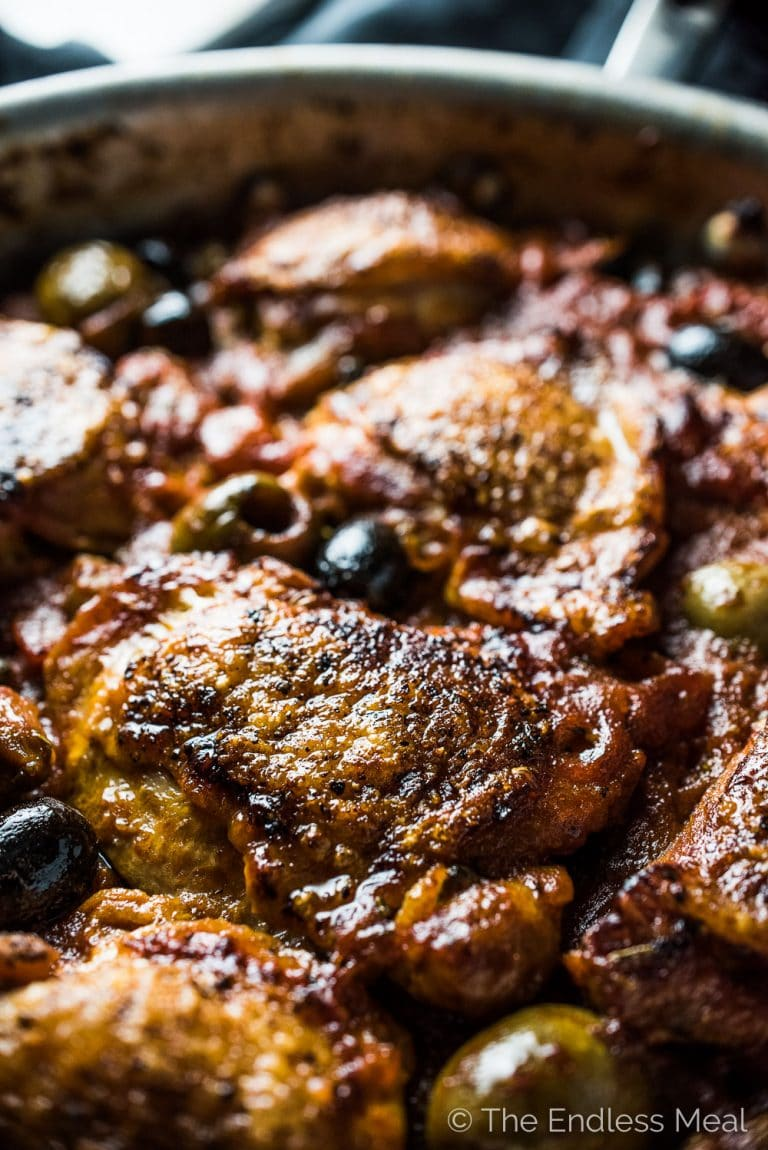 This is my favorite Italian Braised Chicken recipe. The chicken thighs are first seared until the skin is crispy then they're gently simmered in a delicious tomato and olive sauce. The chicken becomes super flavorful and tender. This is a healthy dinner recipe you don't want to miss. | paleo + gluten-free + Whole30 compliant| theendlessmeal.com | #italianchicken #chicken #chickenrecipes #healthyrecipes #whole30recipes #paleorecipes #glutenfreerecipes