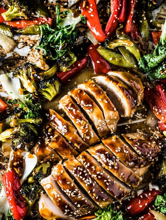 A sheet pan filled with peppers, broccoli and bok choy and 2 sliced Asian glazed chicken breasts.