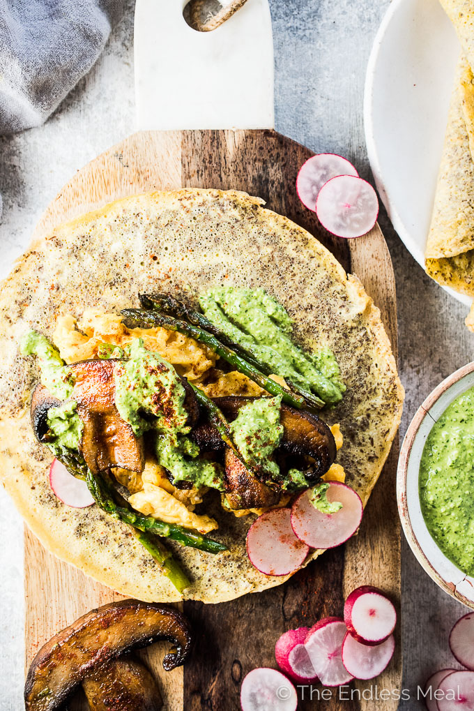 Who knew that healthy Mushroom Breakfast Tacos could be so delicious? Soft scrambled eggs, smoky portobello mushrooms, crisp asparagus, and pesto are all wrapped up in easy to make flax seed and egg tortillas. These pretty crepe like tacos make a great make-ahead brunch recipe or meal-prep for weekday mornings. You will LOVE them! | vegetarian + gluten-free + paleo | theendlessmeal.com | #vegetarian #breakfasttacos #tacos #paleo #brunch #cincodemayo #breakfast