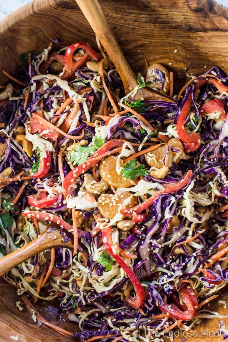 SAVE FOR LATER: This colorful and delicious Asian Coleslaw Recipe makes the perfect side to any BBQ. It's loaded with crunchy veggies, mandarin oranges, and roasted cashews and tossed in a (mayo-free!) creamy orange sesame dressing. You will LOVE it! | vegan + paleo + gluten-free | #theendlessmeal #coleslaw #asiancoleslaw #salad #asiansalad #sesamedressing #vegan #nomayocoleslaw #paleo #healthycoleslaw