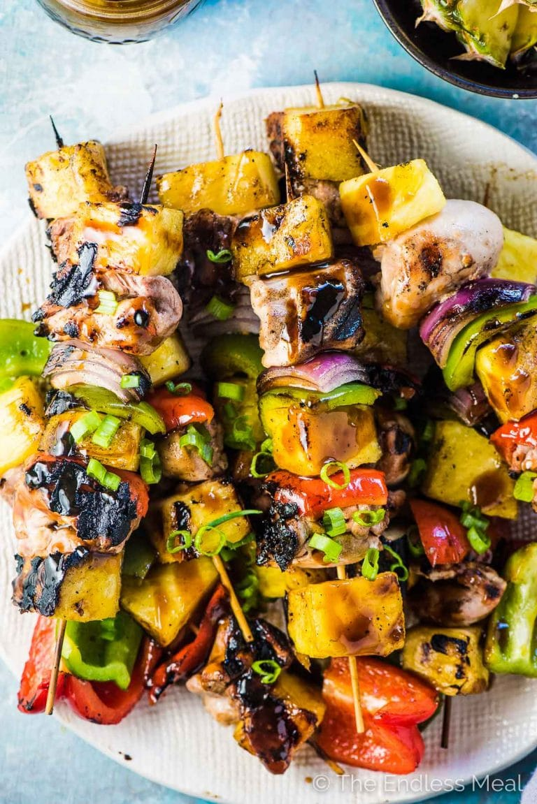 SAVE FOR LATER! Grilled Hawaiian Chicken Skewers are threaded with juicy marinated chicken, sweet pineapple, and crunchy peppers and onions. Once they're grilled to perfection they're drizzled with an easy to make (and refined sugar-free!) tasty teriyaki sauce and served with either coconut rice or healthy coconut cauli rice.  | paleo + gluten-free + refined sugar-free | #theendlessmeal #hawaiian #hawaiianchicken #chicken #chickenkebabs #chickenskewers #bbq #grill #grilledchicken #pineapple
