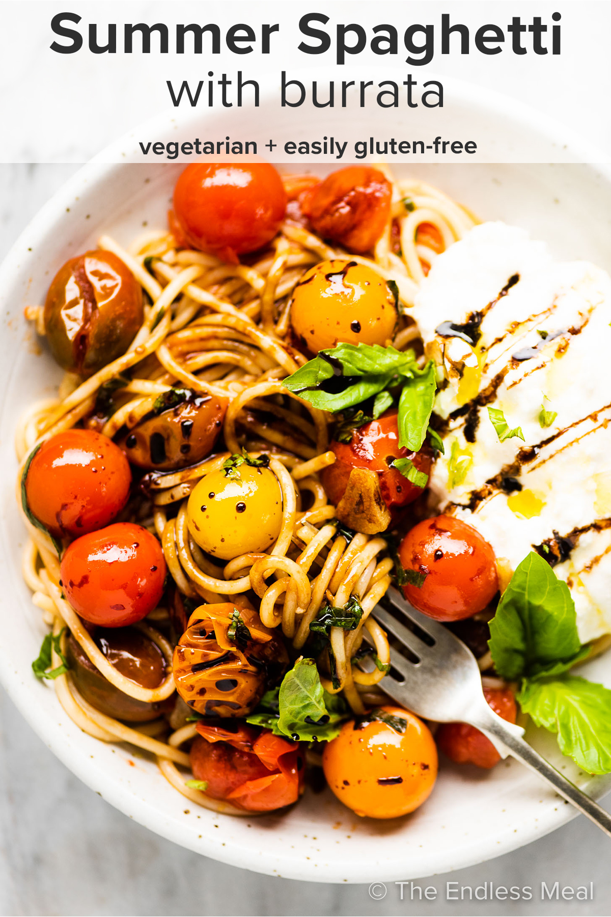 Summer spaghetti in a white plate with burrata and the recipe title on top of the picture.