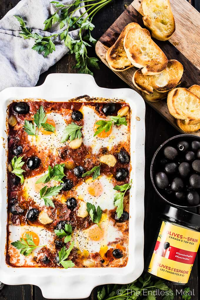 Spanish Baked Eggs is made with a rich tomato sauce with whole cloves of roasted garlic and lots of plump, black Hojiblanca Olives from Spain. Eggs are baked into the sauce which is just as delicious eaten for dinner as it is for breakfast. | gluten-free + paleo + Whole30 + vegetarian option | #theendlessmeal #eggs #spanisheggs #olives #bakedeggs #breakfast #brunch