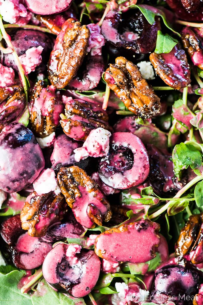 A close up of this arugula and fresh cherry salad with cherry vinaigrette poured over the top.