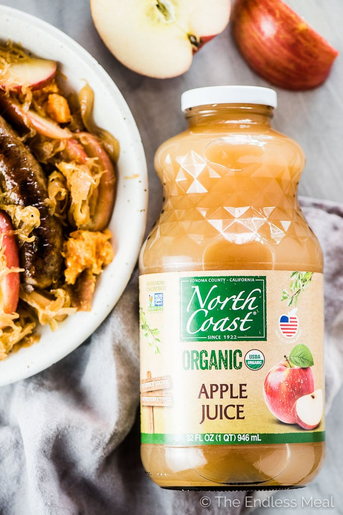 A bottle of North Coast Organic Apple Juice beside a plate of bratwurst and sauerkraut.