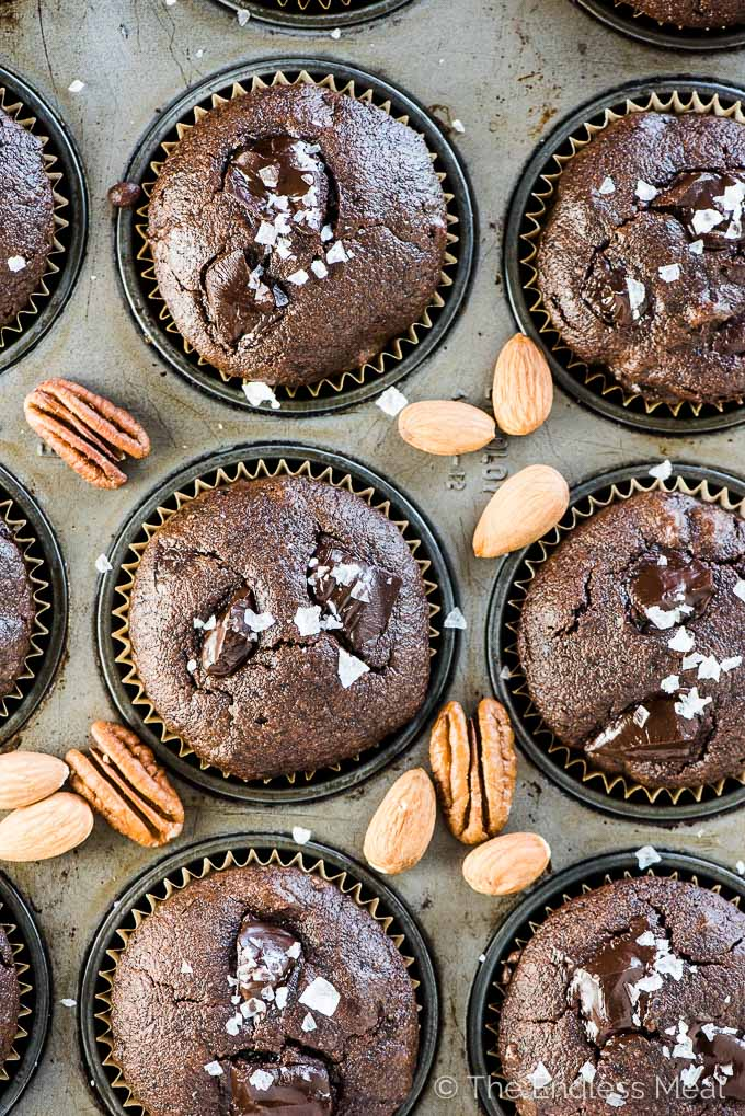A muffin tin filled with chocolate protein muffins fresh out of the oven with some almonds and pecans scattered around them.