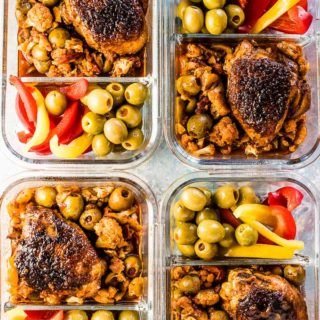 Four meal prep containers filled with Spanish Chicken and Cauliflower Rice with olives and sliced peppers on the side.