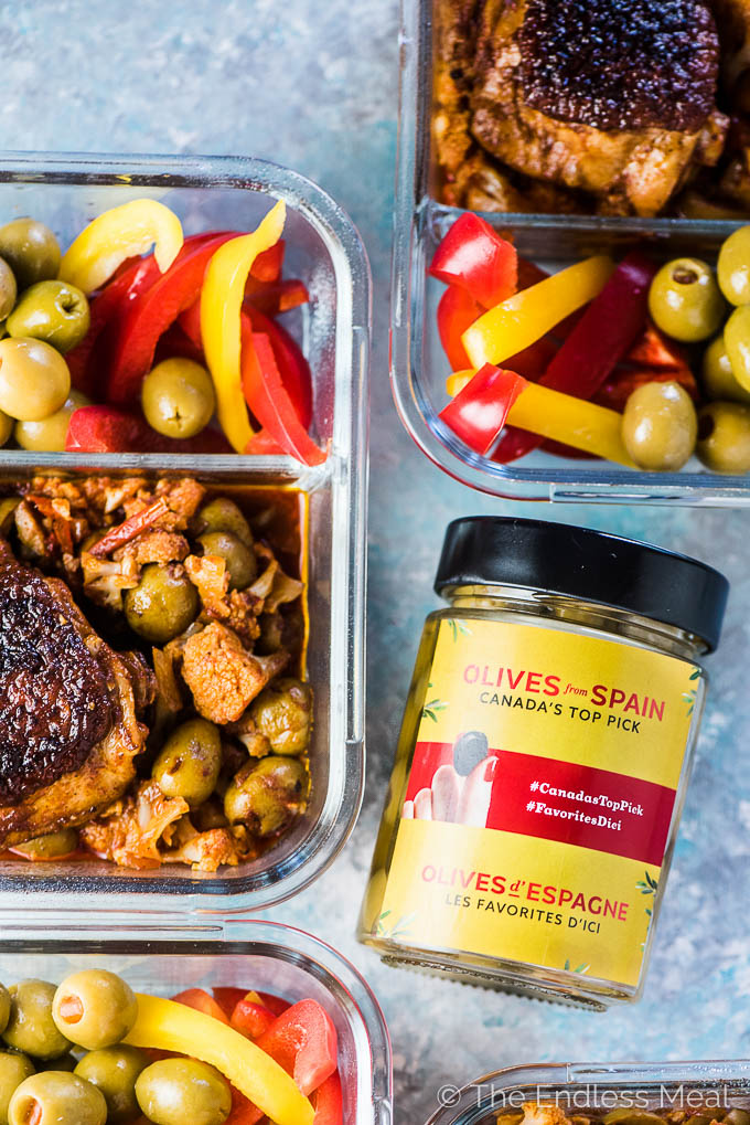 Meal prep containers filled with Spanish Chicken and Cauliflower Rice with olives and sliced peppers on the side and a jar of Spanish olives.