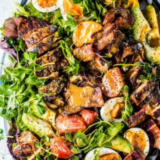 A platter filled with grilled chicken cobb salad with bacon vinaigrette poured over the top