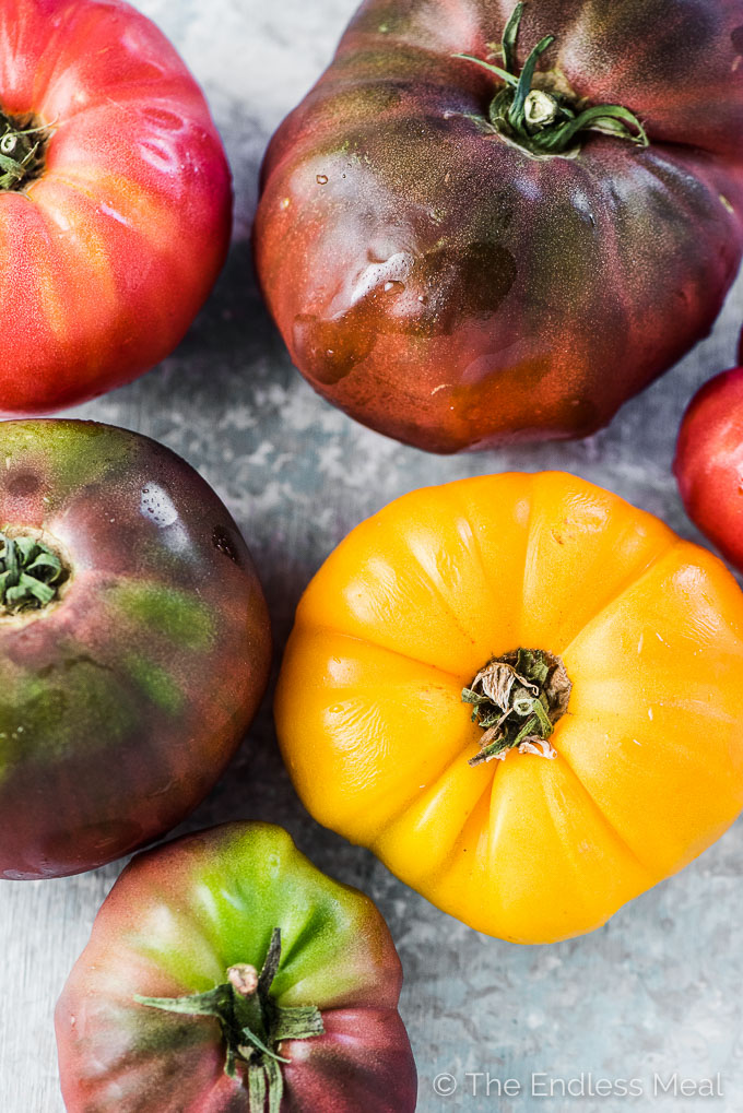 Colorful heirloom tomatoes ready to be chopped and put into the grilled chicken cobb salad.