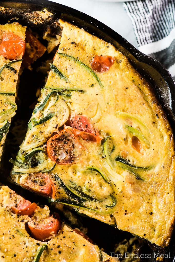 Looking down on a thick slice of zucchini noodle frittata in a cast iron frying pan.