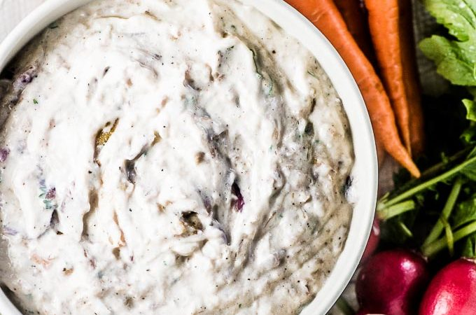 A bowl filled with yogurt and roasted caramelized onion dip with vegetables on the side for dipping.