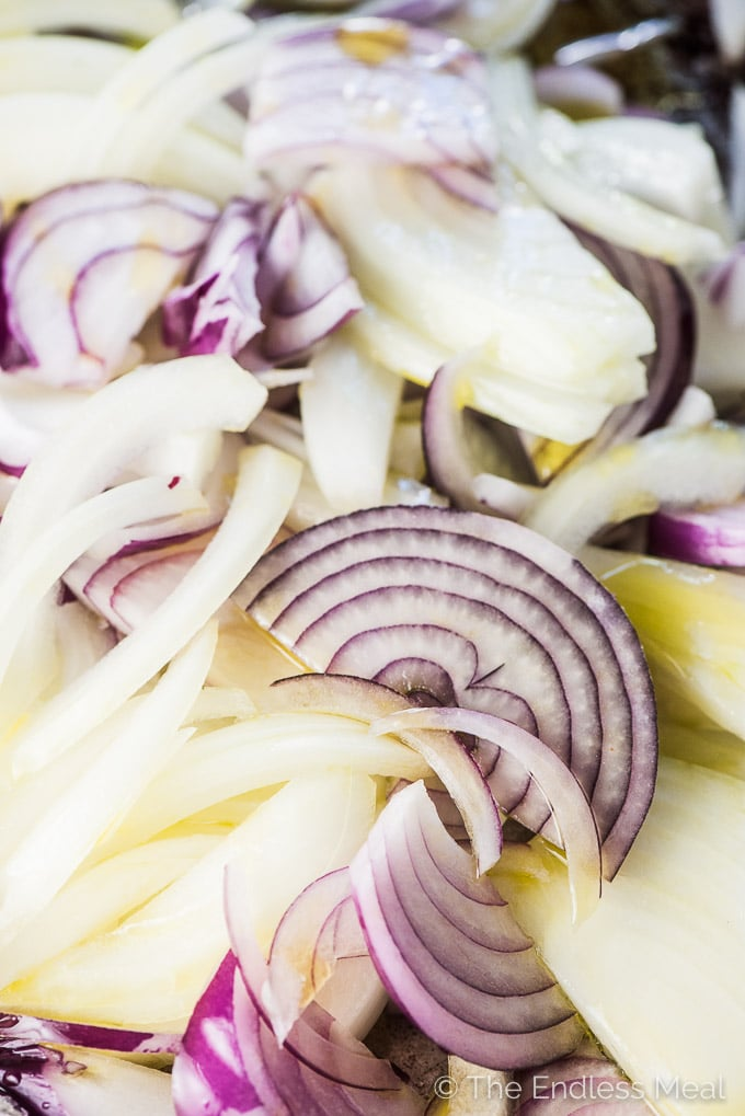 A baking tray will filled onions covered in olive oil ready to be roasted and turned into caramelized onion dip.