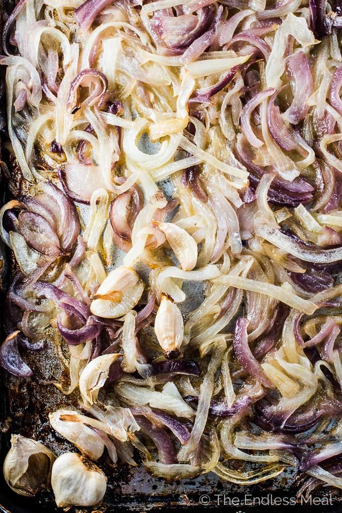 A baking tray will filled roasted onions and garlic that are ready to be turned into caramelized onion dip.