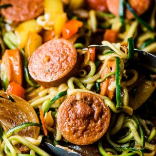 A close up picture of sausage and peppers in a pan with zoodles and a pair of kitchen tongs.