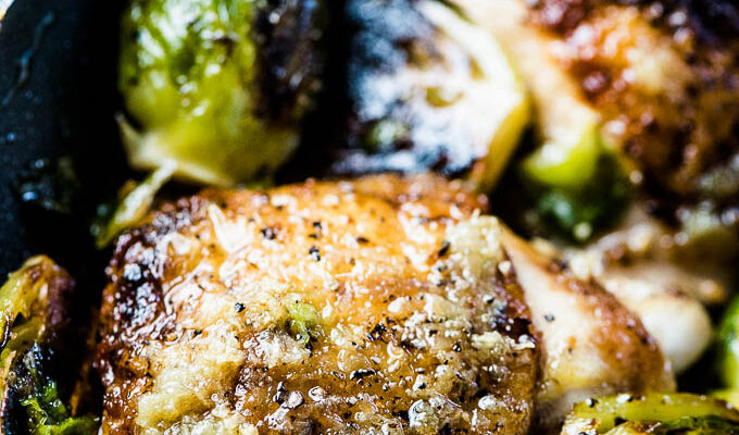 A close up of garlic butter chicken and brussels sprouts in a pan.