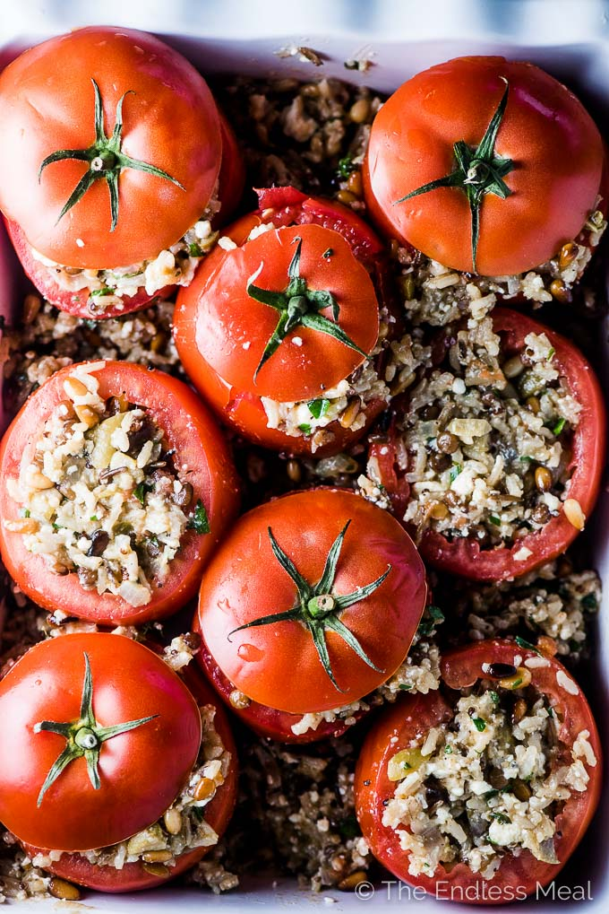 Tomatoes stuffed with rice in a baking dish ready to go into the oven.
