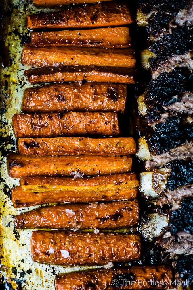 Roasted caramelized carrots on a baking sheet beside a rack of blackened ribs.