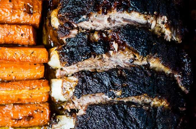 Blackened ribs beside caramelized carrots on a sheet pan.