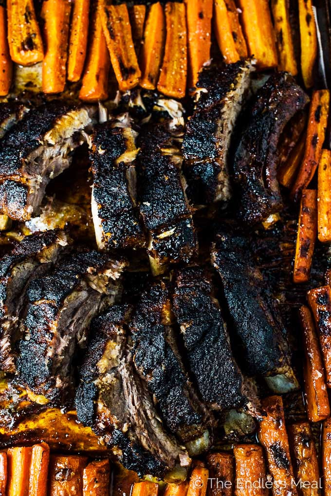 SAVE FOR LATER! Blackened Ribs with Caramelized Carrots is a ridiculously delicious and easy to make dinner recipe. The black and orange color scheme makes it perfect for a fall/ Halloween dinner, but you're going to want to make them again all winter long. | gluten-free + refined sugar-free + paleo | #theendlessmeal #ribs #porkribs #backribs #spareribs #sheetpandinner #onepandinner #paleo #glutenfree #refinedsugarfree #halloween #fall #fallrecipes #healthyrecipes #carrots #blackened