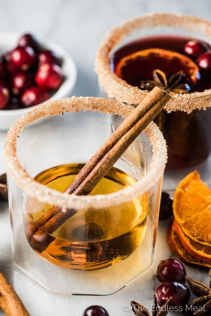 A glass of bourbon with a sugared rim and a cinnamon stick in it waiting to be made into a cranberry hot toddy.