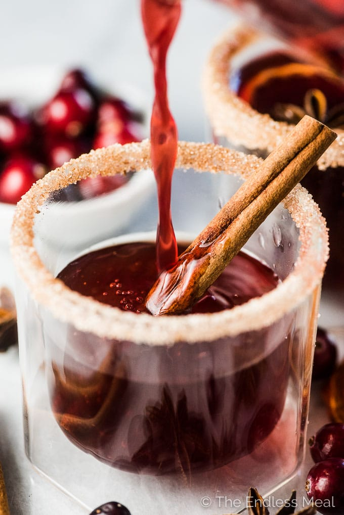 Making a cranberry hot toddy by pouring spiced cranberry juice into a glass.