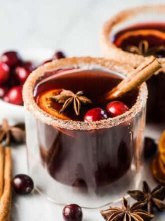 A glass of spiced cranberry hot toddy with a cinnamon stick.