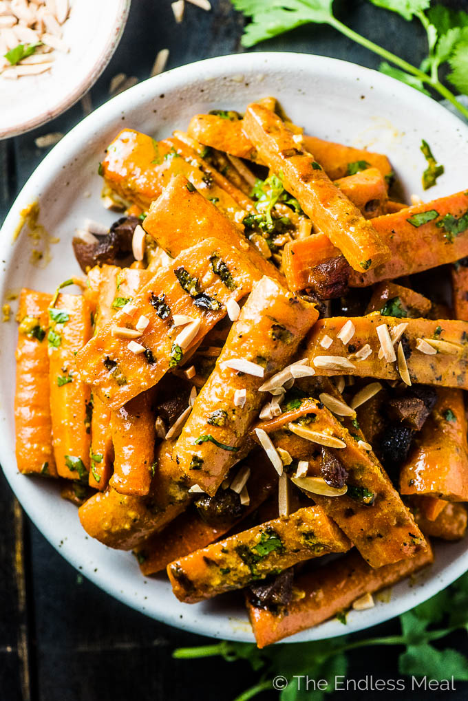 A closeup of curry grilled carrots in a white serving dish with some slivered almonds sprinkled on top.