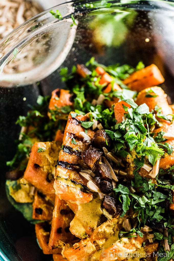 A glass bowl filled with grilled curry carrots with the tandoori yogurt sauce, almonds, raisins, and parsley on top.