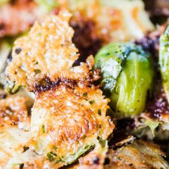 A close up shot of parmesan brussels sprouts with melted parmesan cheese sticking to the cut edge of the brussels.