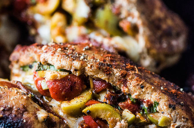 Spanish Stuffed Pork Chops in a pan with melted cheese and olives.