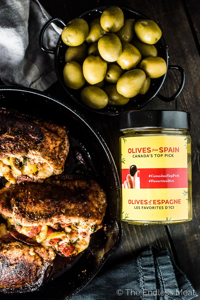 Spanish Stuffed Pork Chops on a black table with a jar and bowl of green Gordal olives from Spain.